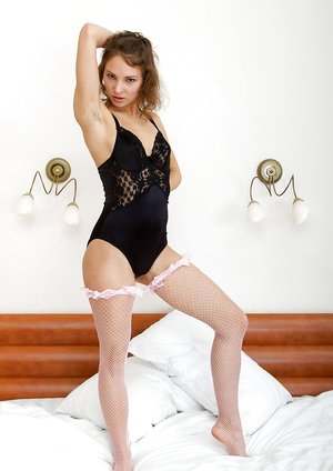 Simona strips from lingerie and stockings on bed